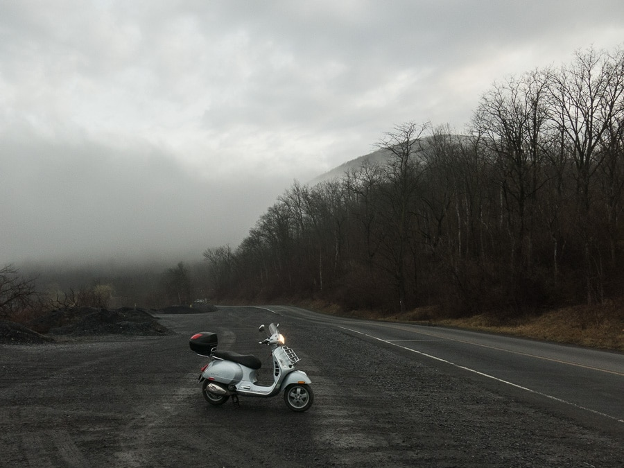 Vespa and fog breaking over a mountain