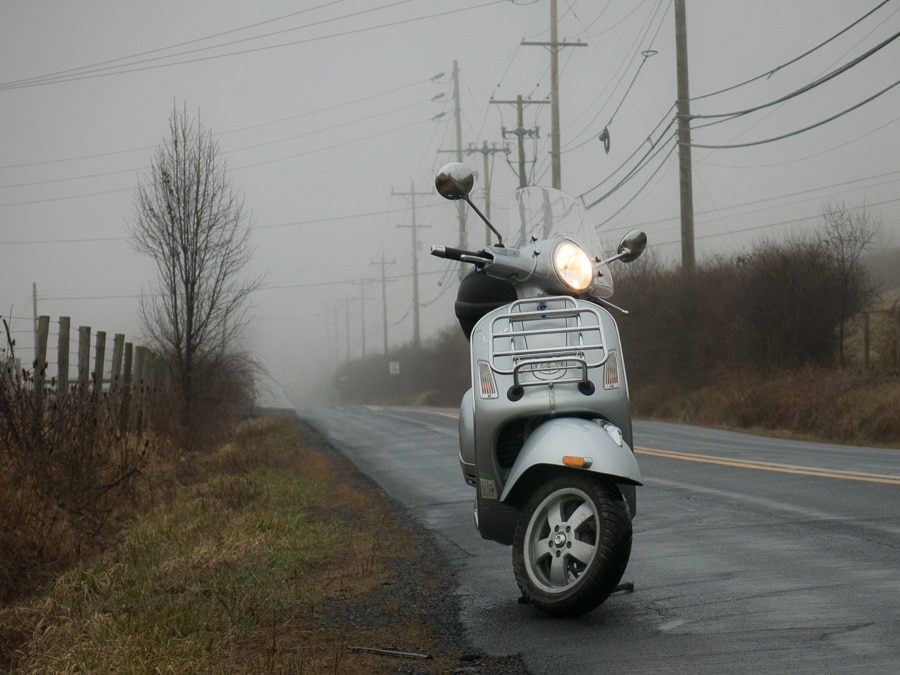 Vespa in the fog along a rural road