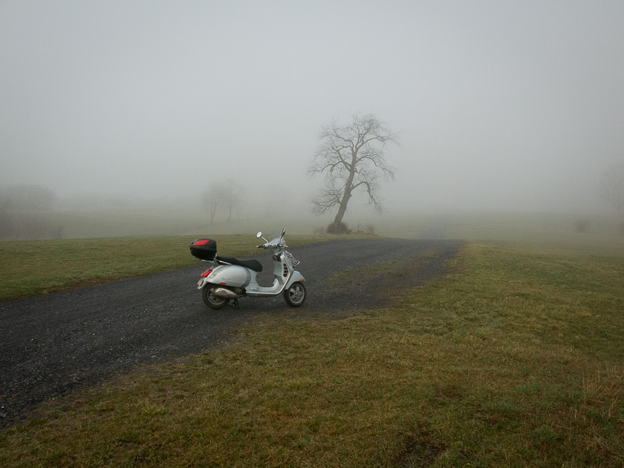 Vespa in the fog on a rural gravel road
