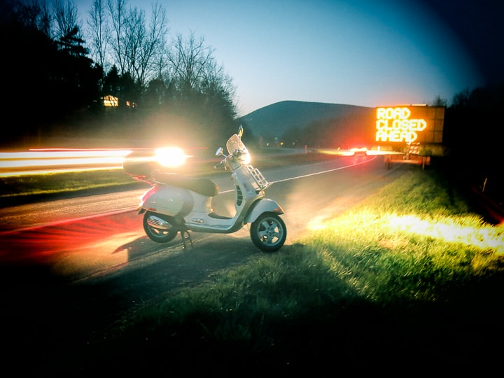 Vespa GTS scooter along road at night with passing cars