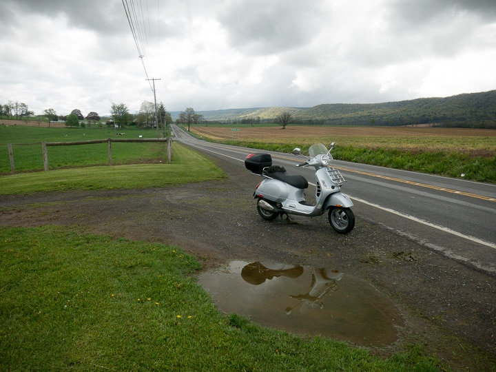 Vespa GTS scooter along a rural road on a gray day