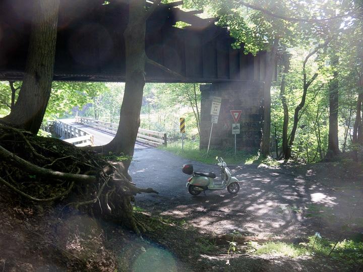 Vespa GTS scooter under a railroad bridge