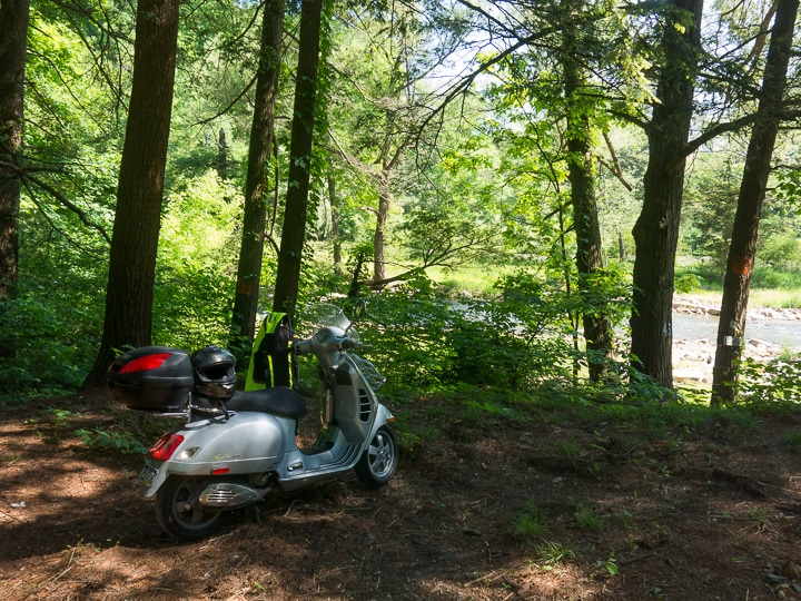 Vespa parked in the woods along a stream