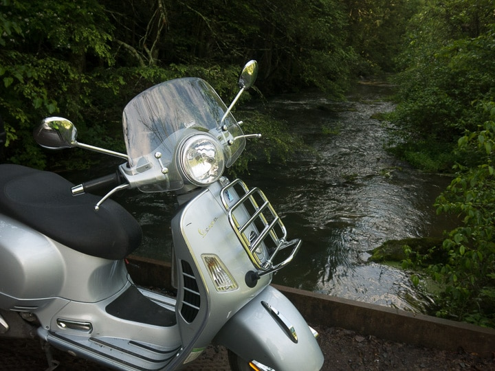 Vespa GTS scooter along a small stream