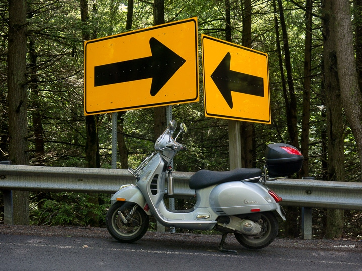 Vespa GTS scooter with conflicting road signs