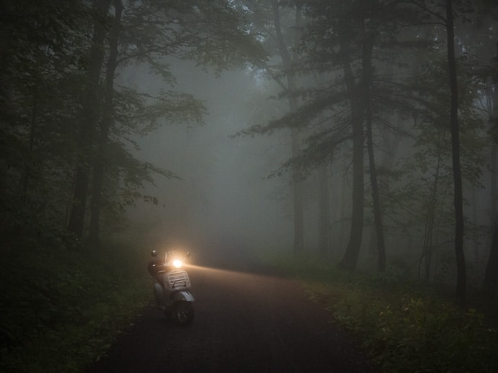 Vespa GTS scooter on fog shrouded forest roac