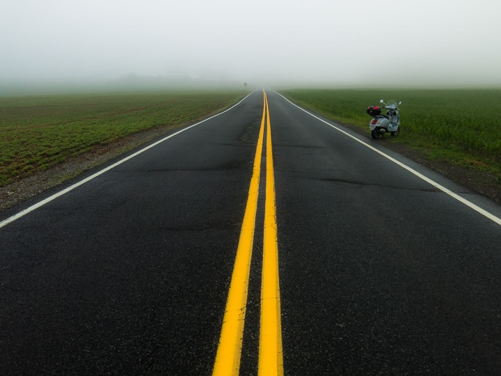 Yellow lines on foggy road with Vespa GTS scooter