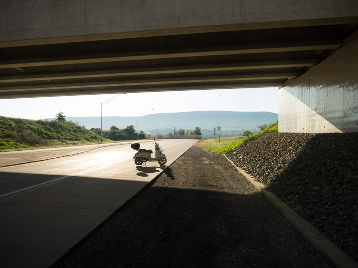Vespa GTS scooter along freeway exit in the morning light