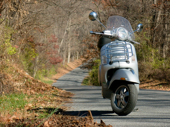 Vespa GTS scooter on a winding forest road