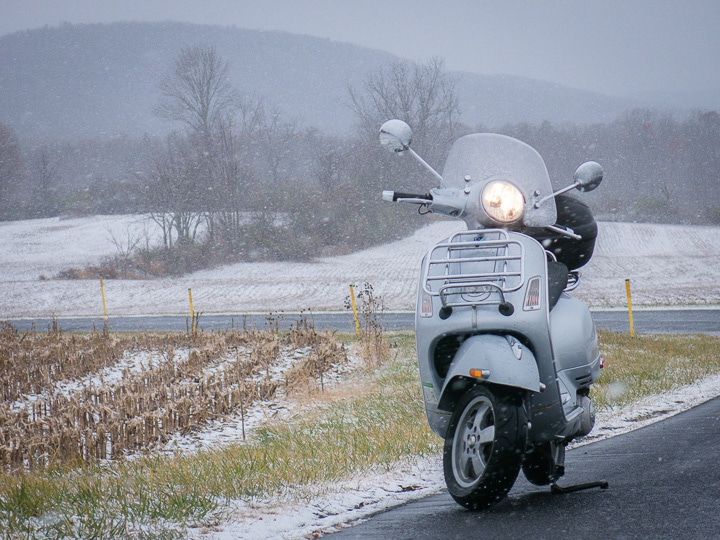 Vespa GTS scooter on a rural road during a snow flurry