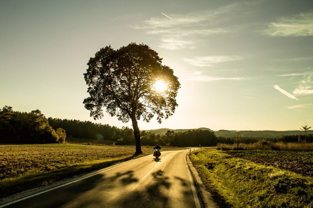 motorcycle on country road at sunset