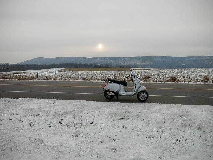 Vespa GTS along rural road in snow