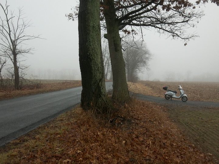 Vespa GTS scooter in fog along road