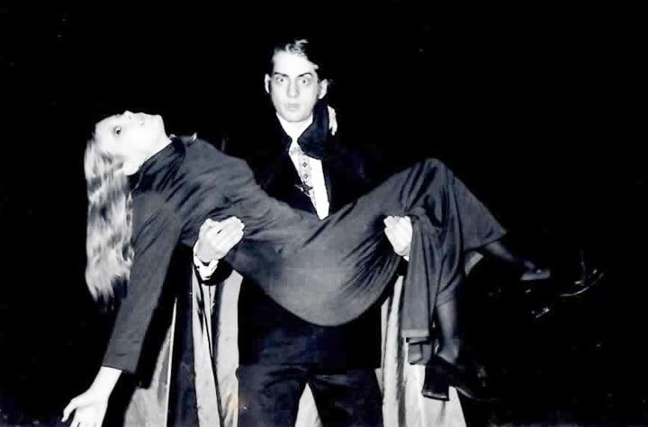 Vampire holding woman at night in graveyard