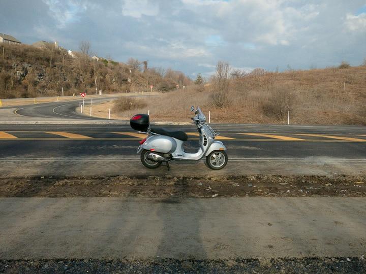 Vespa GTS scooter along highway at sunrise