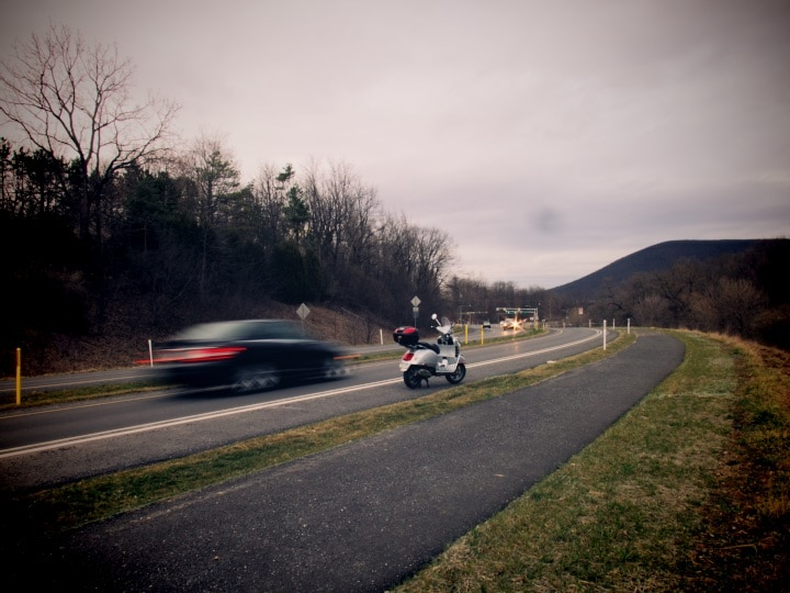 Vespa GTS scooter along road on a cold day