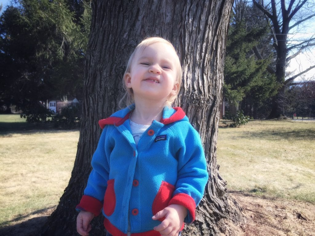 Laughing toddler standing in front of a tree