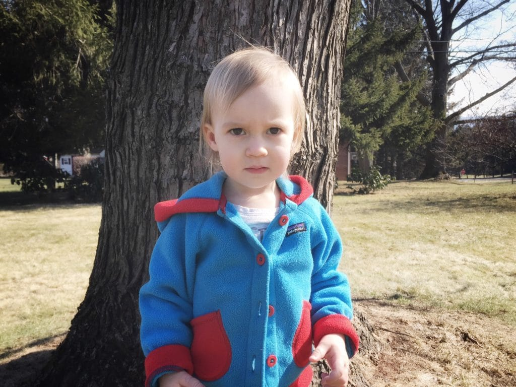Toddler named Emma standing in front of a tree