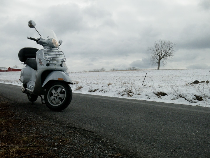 Vespa GTS scooter on a rural road in winter