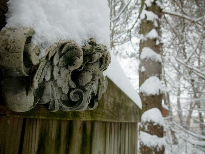 snow covered angel sculpture in garden