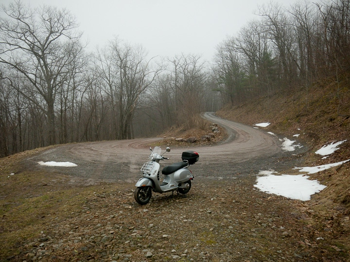 Vespa GTS scooter on muddy mountain road
