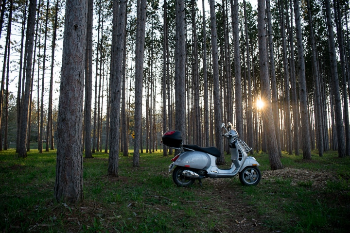 Vespa GTS scooter in the woods at sunset