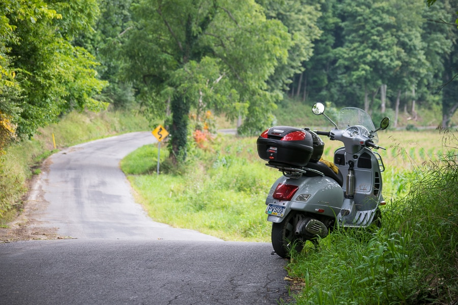 Vespa GTS scooter parked along a country road