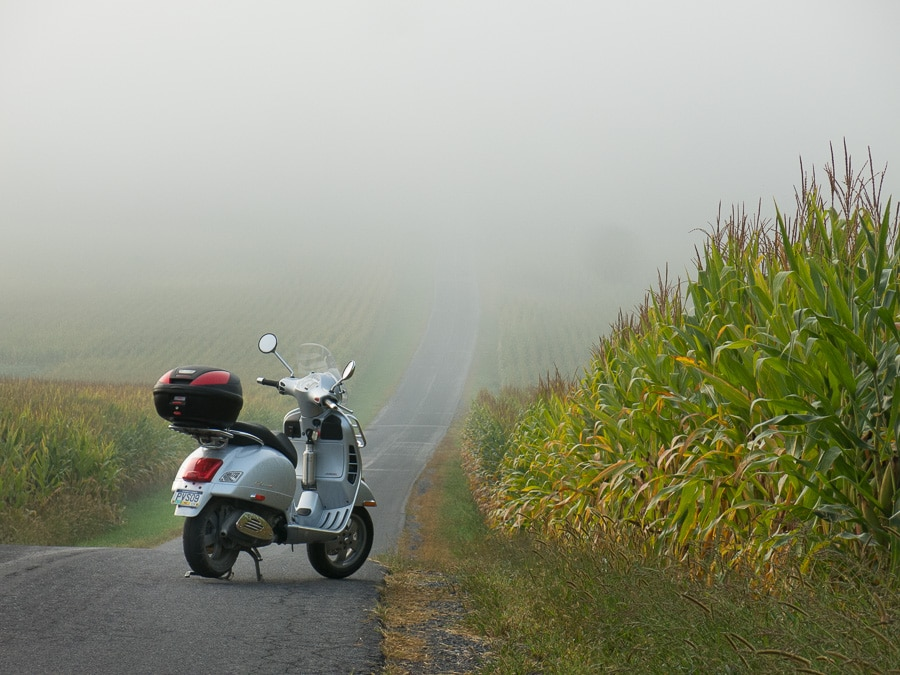Vespa GTS scooter on foggy rural road