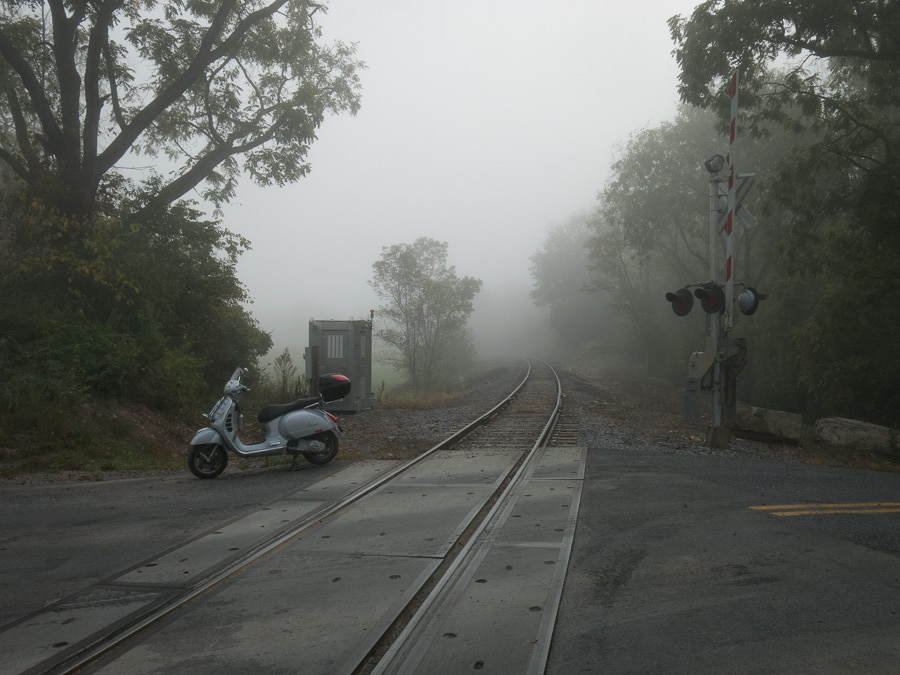 Vespa GTS scooter in fog along railroad tracks