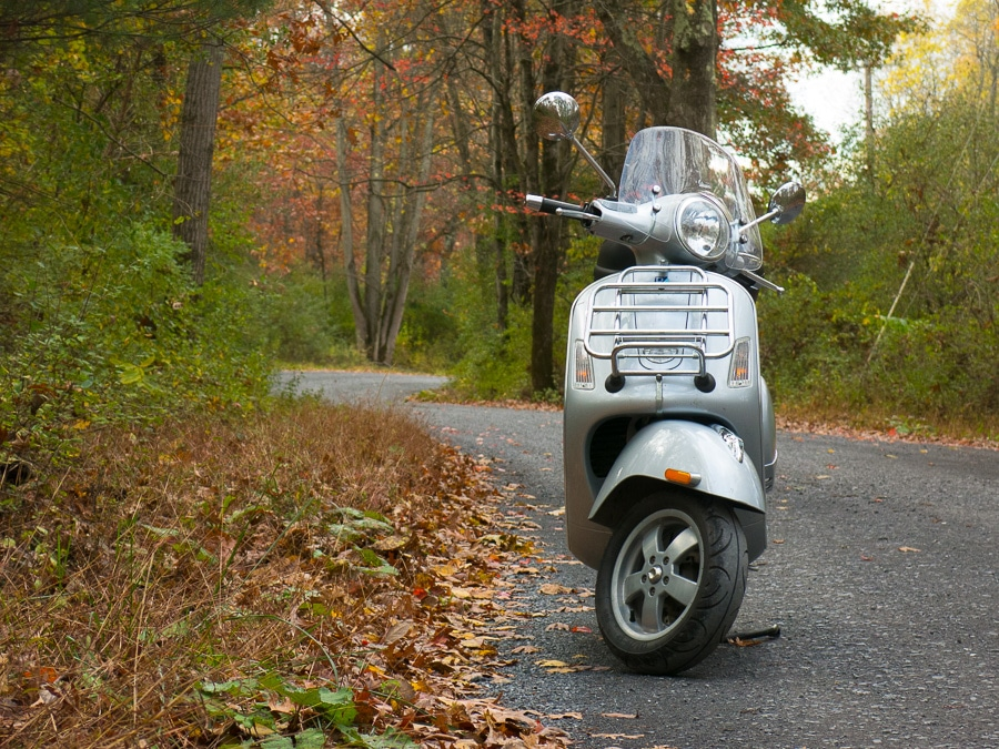 Vespa GTS scooter on road through the woods