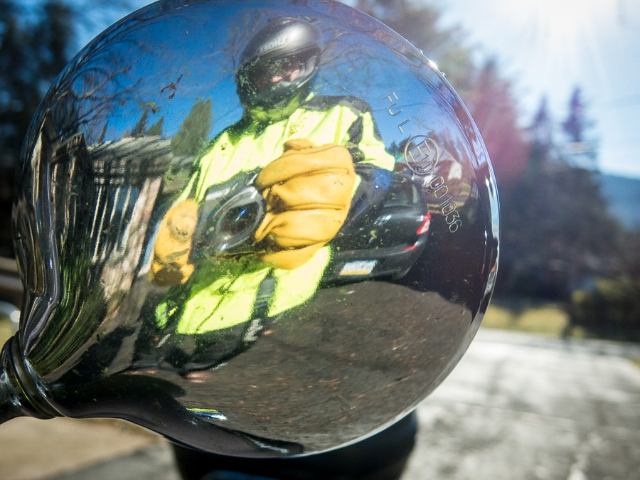 Reflection of Vespa rider Steve Williams on the back of the scooter mirror