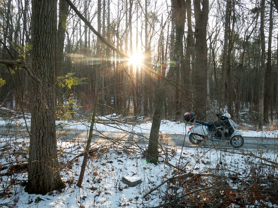 Vespa GTS scooter in winter woods at sunset