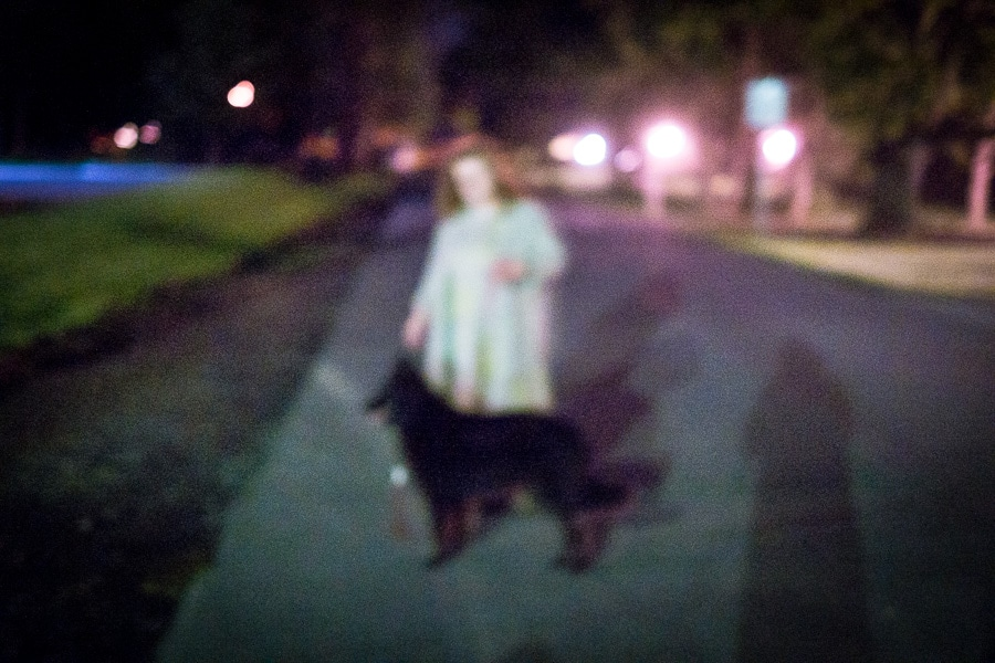 Woman and dog on street at night