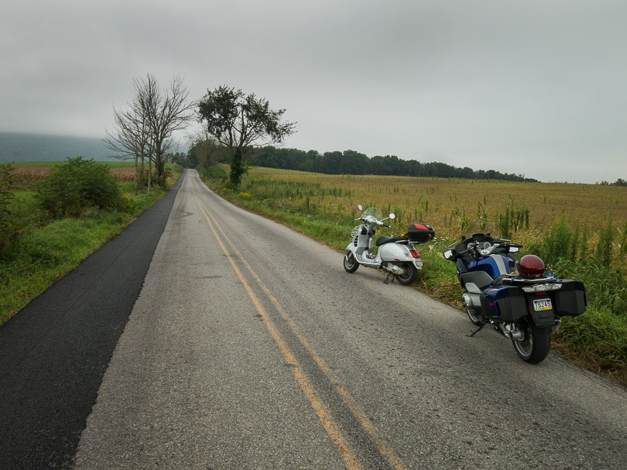 Vespa GTS scooter and BMW R1200 RT along rural road