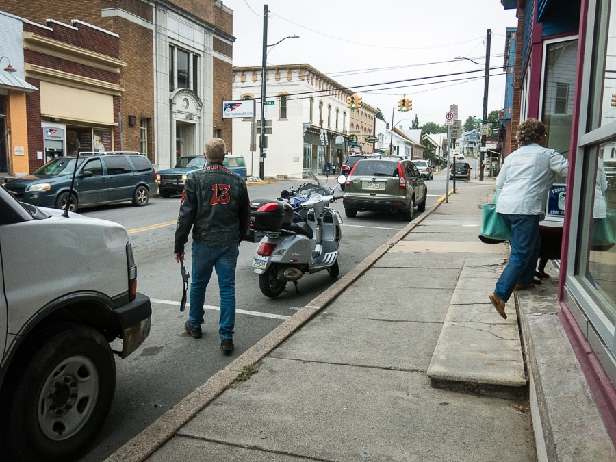 Paul Ruby walking to his BMW motorcycle parked on the street in Millheim, Pennsylvania
