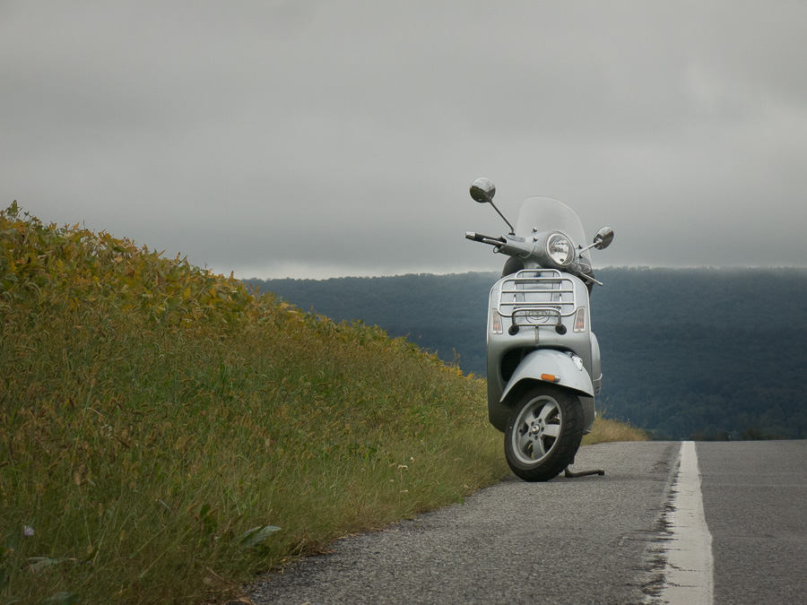 Vespa GTS scooter on gray day along rural road