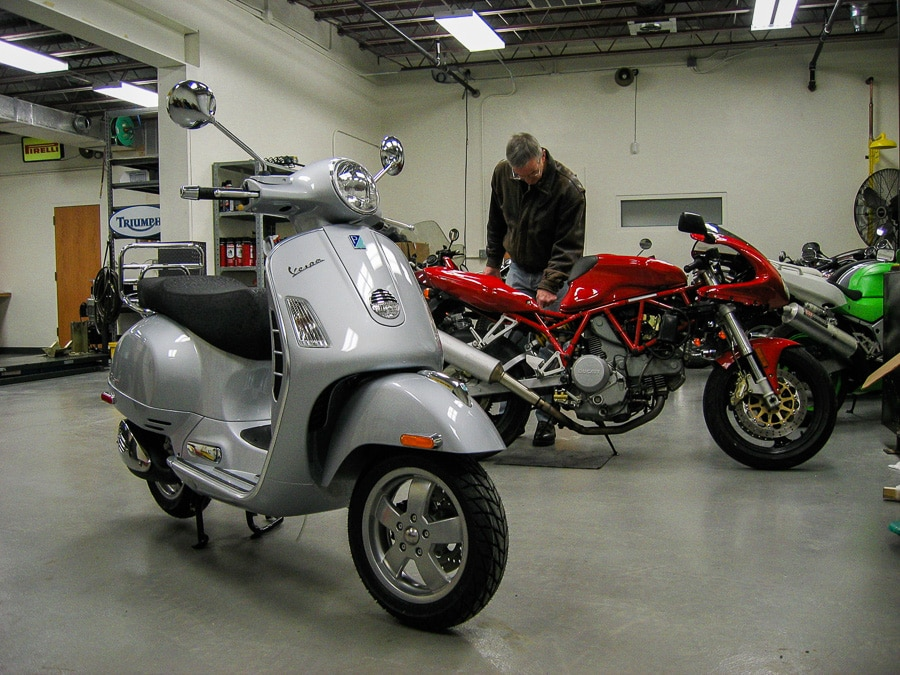 Vespa GTS scooter and Ducati motorcycle in shop