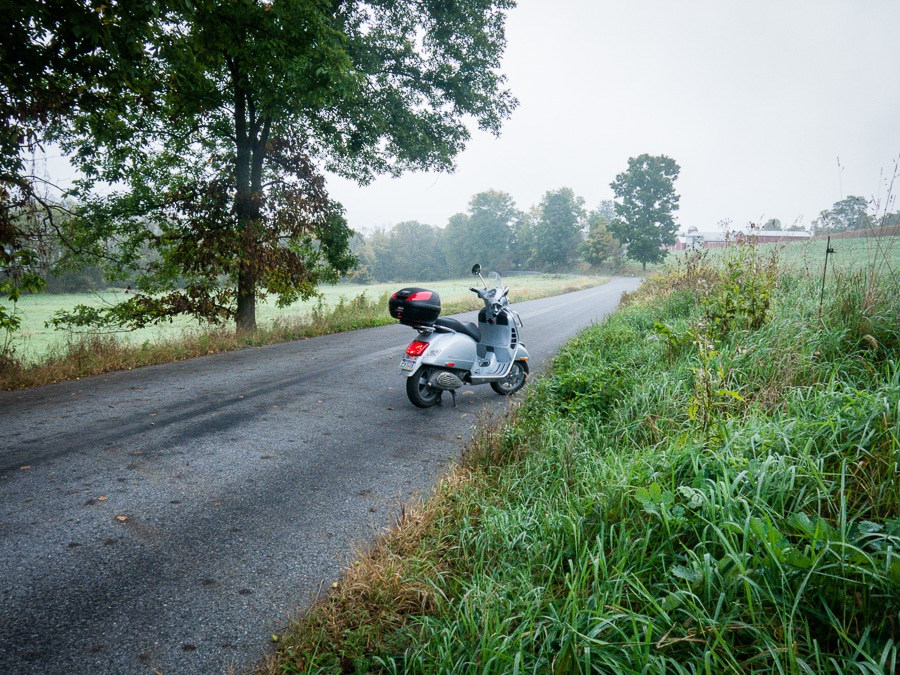 Vespa GTS scooter along rural road on a foggy day
