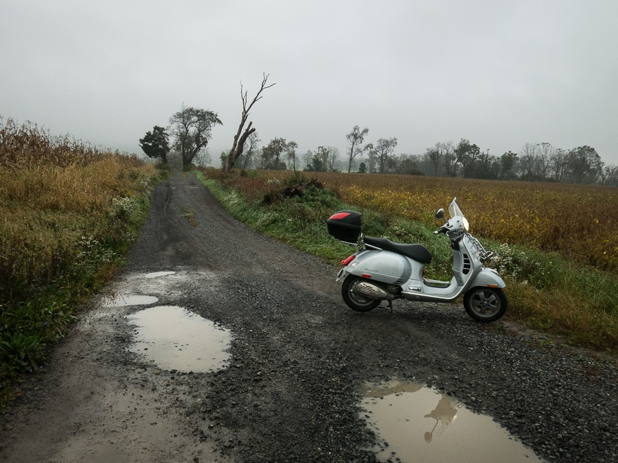 Vespa GTS scooter on a wet gravel road
