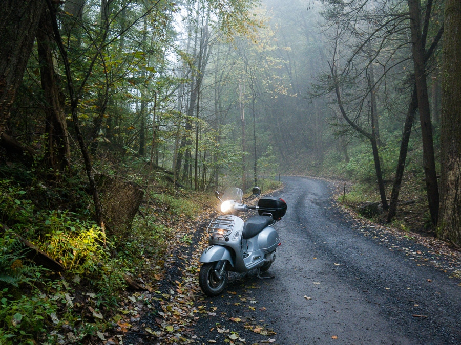 Vespa GTS scooter on a gravel forest road in the fog